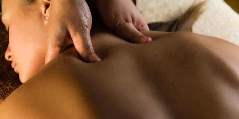 Massage Therapist relaxes client's neck and shoulder muscles